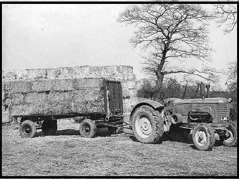 A Massey Harris Tractor pulling a trailer loaded with bales.